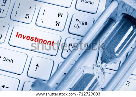 Financial and long term sustainable investment concept : White push button on a desktop computer keyboard inscribed or printed with a red word Investment, and a sandglarss or hourglass nearby. #712729003