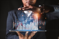 Financial arrangement plan concept stock market chart Suit wearing businessmen are showing a virtual hologram that boosts revenue with a dark color scheme.