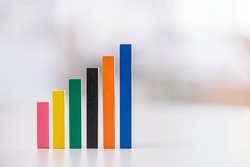 Financial business growth or sales performance increase concept : Increasing height, color wood bar graphs on a table, depicts increasing of productivity or challenging amount on competitive market