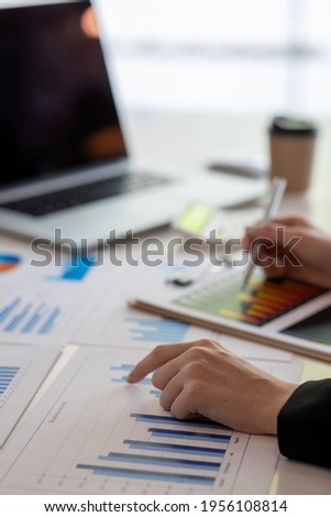 Financial Business woman analyze the graph of the company's performance to create profits and growth, Market research reports and income statistics, data,repotr,Financial and Accounting concept.