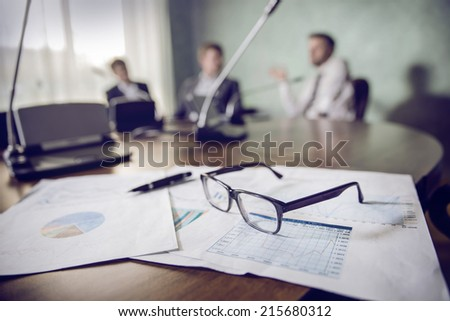 financial chart near dollars seen by unfocused glasses ( colleagues meeting to discuss their future financial plans only silhouettes being viewed )