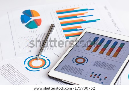 Financial charts on the table with tablet and pen