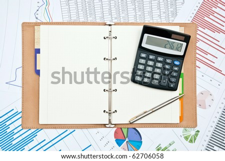 Financial charts with calculator,pen,notebook and pen