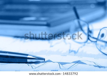 Financial charts with laptop with shallow depth of field