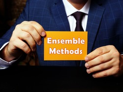 Financial concept about Ensemble Methods with sign on orange business card in hand.