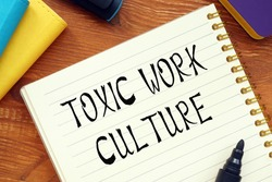 Financial concept about TOXIC WORK CULTURE question marks with phrase on the page.