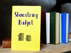 Financial concept meaning Shoestring Budget with inscription on the sheet.
