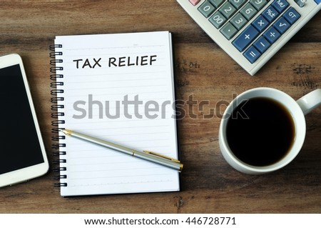 Financial concept - Text Tax relief on a notepad with smart phone, pen, coffee and calculator on a wooden table. #446728771