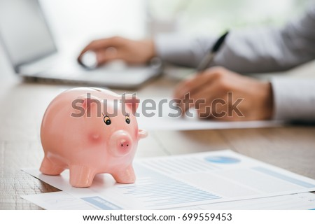 Financial consultant working at office desk and piggy bank on the foreground: insurance, home and investments concept