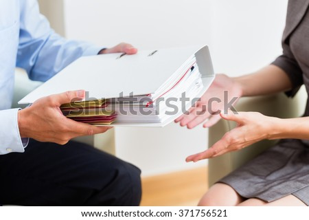 Financial consulting - customer handing over documents to consultant for further analysis Foto stock ©
