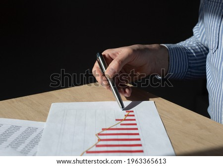 Financial crisis concept. Businessman hand at desk showing at red graph with falling trend, economic decrease, revenue loss, recession, income downturn. Stock foto ©