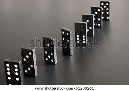 financial crisis concept with domino game on black background