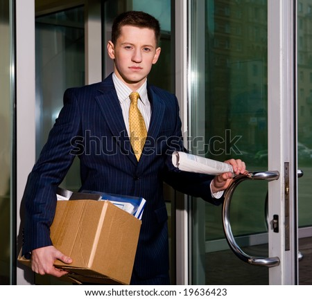 Financial crisis. Unemployed young manager leaving business center in megalopolis