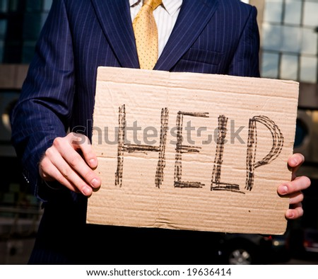 Financial crisis. Unemployment. Businessman holding sign Help outdoors