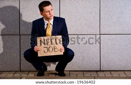 Financial crisis. Unemployment. Young businessman squatting with sign Need Job outdoors