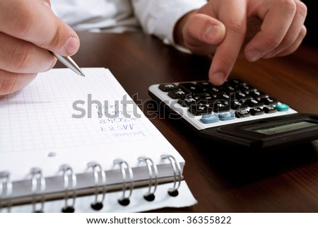 Financial data analyzing. Counting business data on the table closeup - stock photo