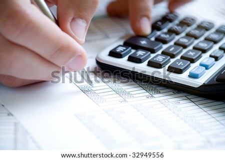 Financial data analyzing. Counting on calculator. Hand with pen on calculator.