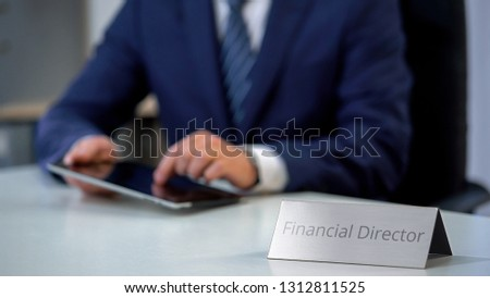 Financial director in suit scrolling on tablet pc, watching corporative files #1312811525