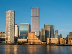 Financial district buildings in Canary Wharf area of London illuminated at sunset against the blue sky