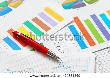 Financial documents and red pen, top view