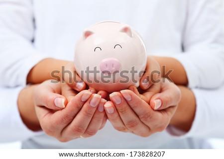 Financial education concept - adult and child hands holding smiling piggy bank - stock photo