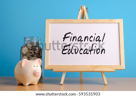 Financial Education,  financial concept. Mason jar with coins inside, piggy bank and whiteboard on wooden table.