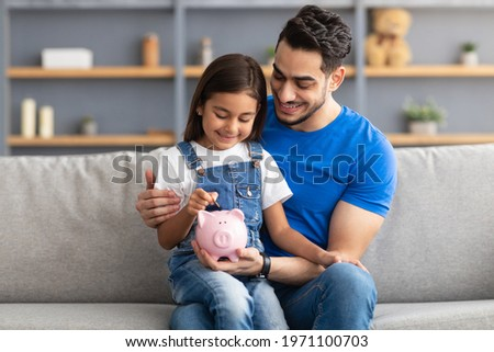 Financial Education For Children Concept. Portrait of smiling little girl putting coin in pink piggy bank, sitting on dad's lap on the couch at home, man teaching his daughter to invest