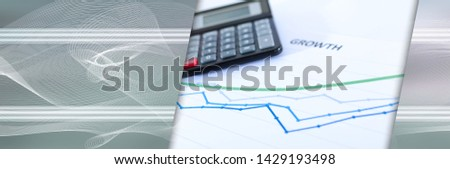 Financial graphs showing growth with calculator closeup. panoramic banner #1429193498