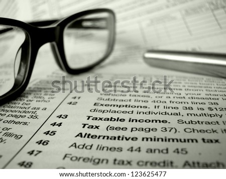 Financial Image Of Some Tax Forms With Glasses And A Pen