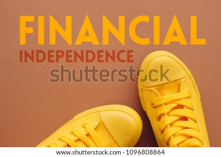 Financial independence concept, young person in yellow sneakers standing over the text, top view