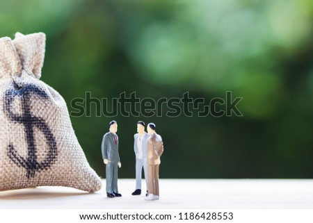 Financial investment negotiation,discussion among CEO or execute level concept: Miniature figurine three businessmen talk on money invest contract agreement, discuss about company direction in future. #1186428553
