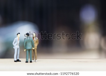 Financial investment negotiation,discussion among CEO or execute level concept: Miniature figurine three businessmen talk on money invest contract agreement, discuss about company direction in future. #1192776520