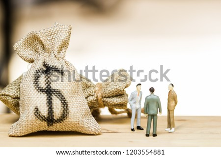 Financial investment negotiation,discussion among CEO or execute level concept: Miniature figurine three businessmen talk on money invest contract agreement, discuss about company direction in future. #1203554881