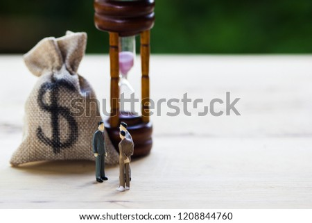 Financial investment negotiation,discussion among CEO or execute level concept: Miniature figurine three businessmen talk on money invest contract agreement, discuss about company direction in future. #1208844760