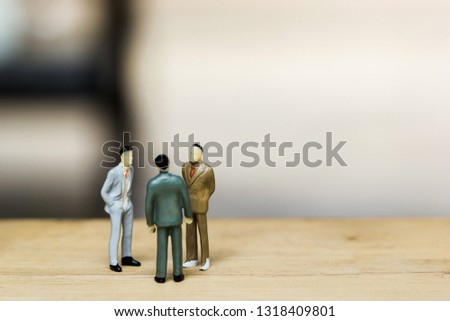 Financial investment negotiation,discussion among CEO or execute level concept. Miniature figurine three businessmen talk on money invest contract agreement, discuss about company direction in future. #1318409801