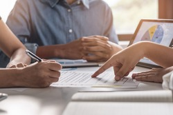 financial investor advisory.  Close up hand pointing at contract and document while sitting together with young couple at the desk in office