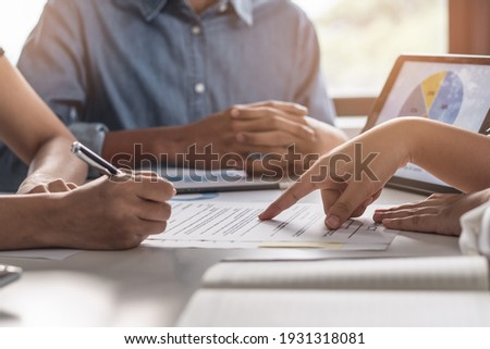 financial investor advisory.  Close up hand pointing at contract and document while sitting together with young couple at the desk in office Stock photo ©