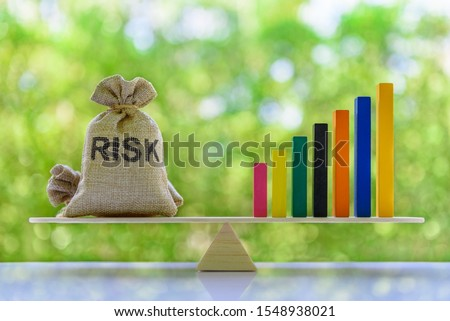Financial leverage and risk management concept : Rising bar graph and risk bags on a basic balance scale, depict the best use of capital based on risk tolerance and willingness to use borrowed fund
