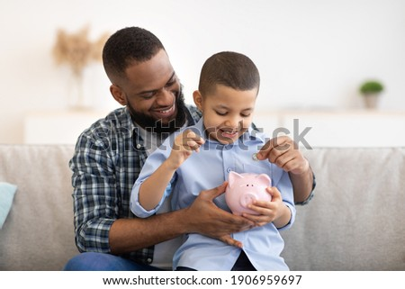 Financial Literacy. Cheerful African Father And Son Putting Money In Piggybank Sitting On Sofa At Home. Daddy Teaching His Child Budget Planning, Keeping Personal Savings Safety