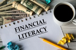 FINANCIAL LITERACY - words on a white sheet against a background of banknotes, cups of coffee and pencil