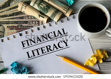 FINANCIAL LITERACY - words on a white sheet against a background of banknotes, cups of coffee and pencil Сток-фото ©