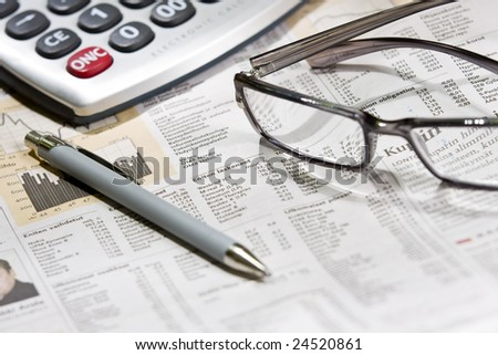 financial newspaper with eye glasses and calculator