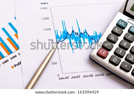 financial performance chart with calculator and pen