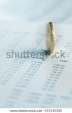 Financial prediction. Coin spinning on financial reports - stock photo