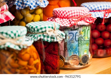 Financial reserves. Money conserved in a glass jar among others preserves. Shallow deep of focus.