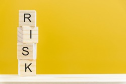 Financial risk assessment and portfolio risk management concept : Stack of vertical 4 or four wood cubes on a table with a letter R, I, S, K on each cube over a yellow background with blank space.