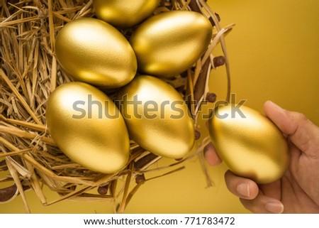Financial success. Man holding a golden egg. Golden Egg on golden background. #771783472