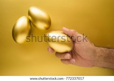 Financial success. Man holding a golden egg. Golden Egg on golden background. #772337017