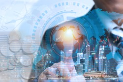 Financial trading stock concept with businessman using wireless network technology to check worldwide market stock data over cityscape night view, IOT internet of things concept