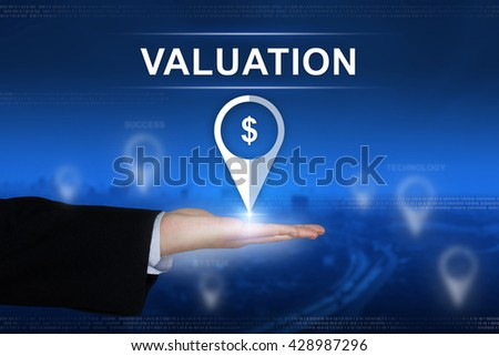 financial valuation button with business hand on blurred background